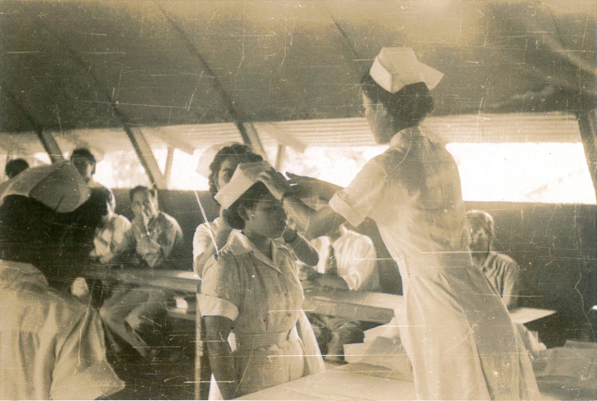 Nurses receiving their nursing caps from Nobu in a Quonset hut-type hospital after the war